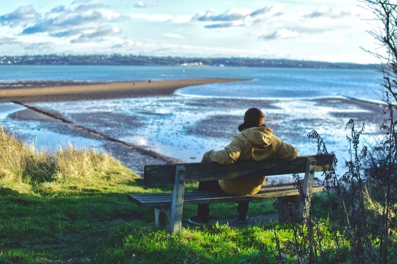 Rear View Of Person Sitting On Bench Against Beach
