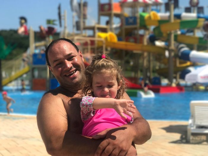 Portrait of happy shirtless father carrying daughter while standing at water park