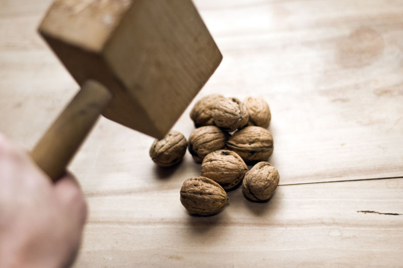 Close-Up Of Person Holding Wooden Hammer Over Walnuts