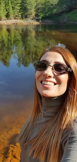 Portrait of smiling young woman with reflection in lake