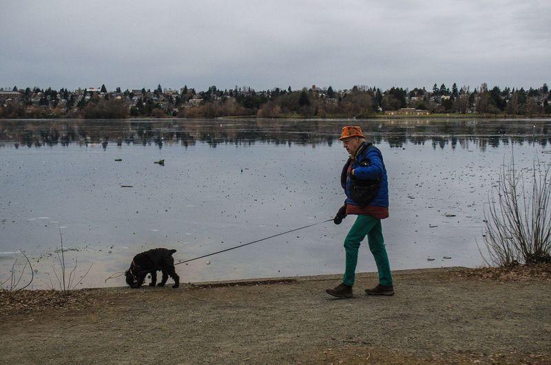 Woman with dog on beach against sky