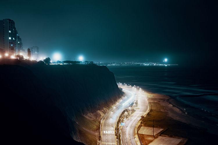 Illuminated city street by sea against sky at night
