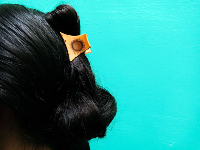 Cropped image of woman with black hair against turquoise background