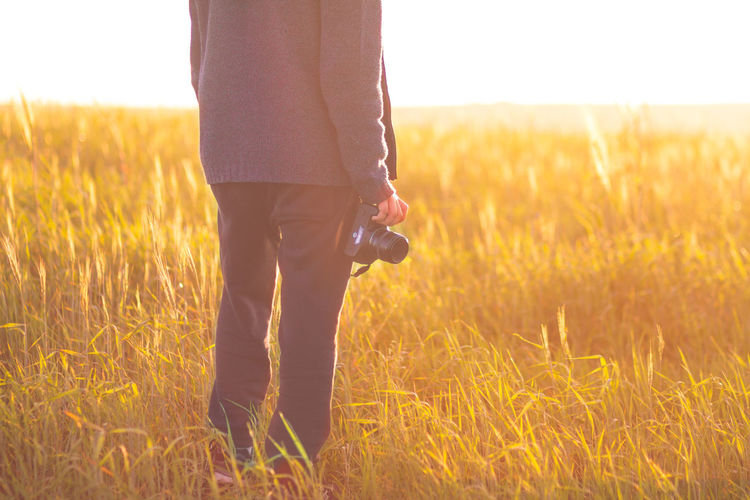 Low Section Of Woman Holding Digital Camera While Standing On Grassy Field