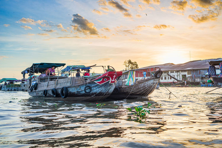 Fishing boats moored on beach against sky during sunset