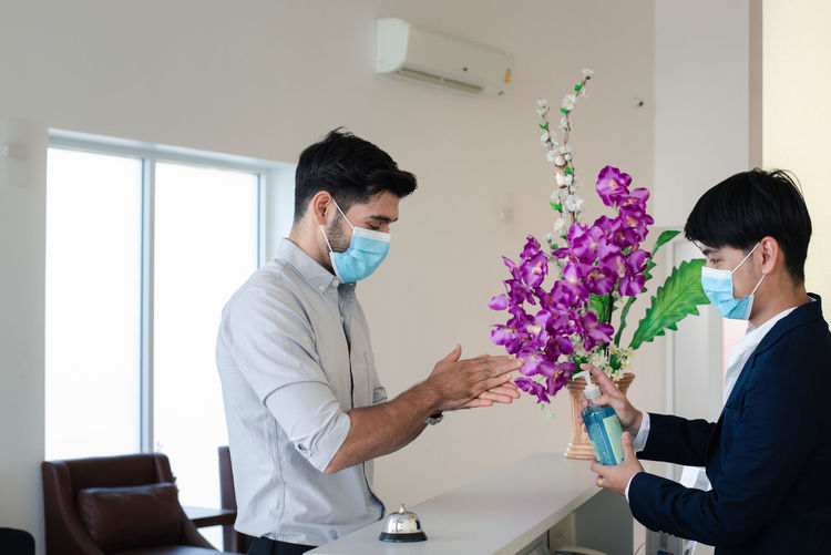 Side view of young businessman wearing mask using hand sanitizer at hotel reception