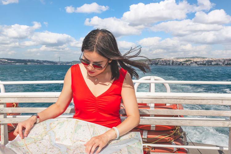 Woman looking at map while sitting by railing in nautical vessel on sea