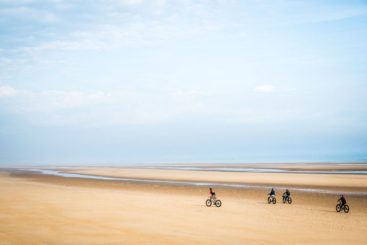 People cycling at beach against sky