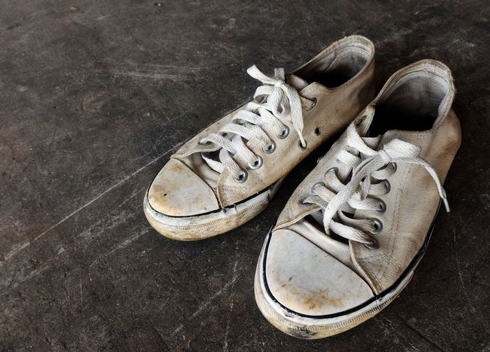 High angle view of weathered white canvas shoes on floor