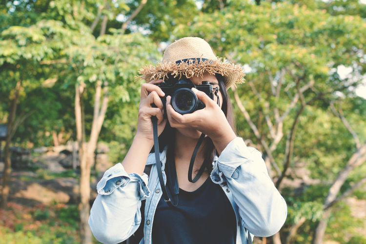 Young woman photographing through camera against trees