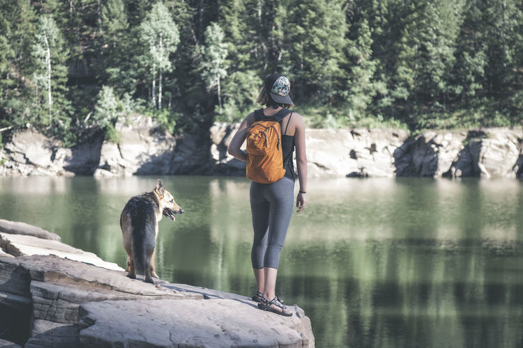Young woman with dog standing on rock by lake
