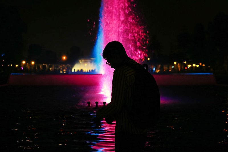 Side view of silhouette man standing against illuminated fountain at night