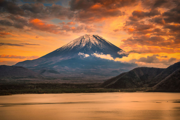 Scenic view of mount fuji mountain against cloudy sky during sunset