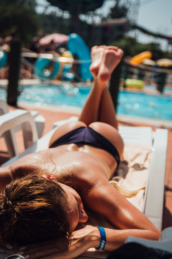 Shirtless woman lying on lounge chair at poolside
