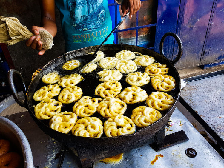 Jalebi an indian sweet dish being fried in sugar syrup in a large container Jalebi Business Cooking Pan Day Food Food And Drink Freshness Fried Sweets Healthy Eating High Angle View Household Equipment Human Body Part Incidental People Jilipi Kitchen Utensil Market Market Stall One Person Outdoors Preparation  Preparing Food Retail  Snack Sugar Syrup Sweet Dish