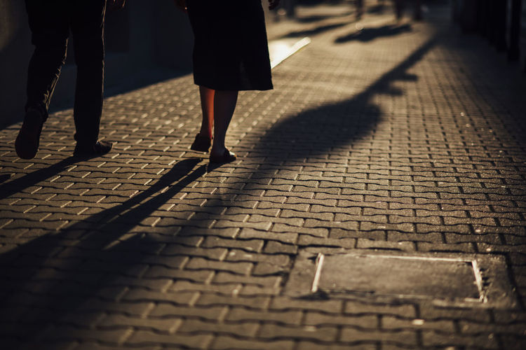 Low section of people walking on street