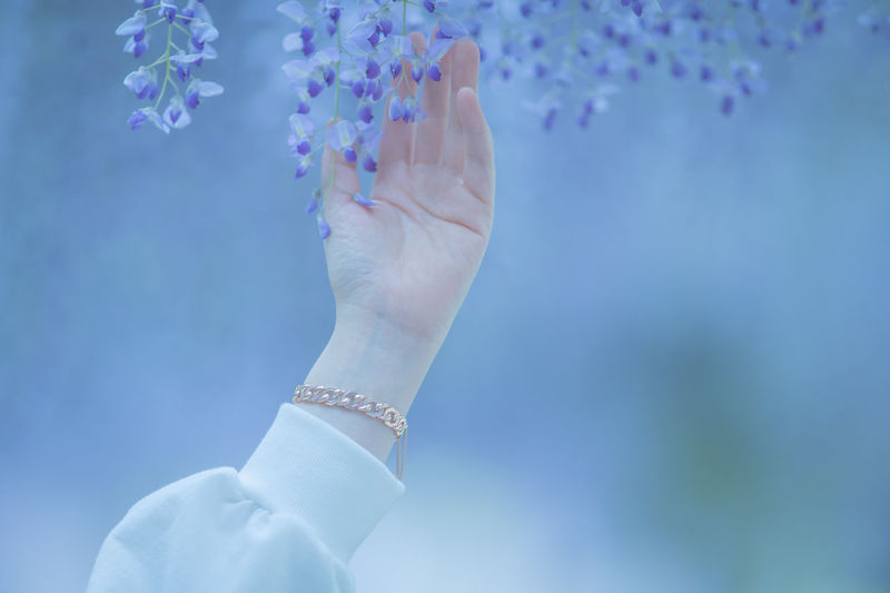 Close-up of woman holding hands against blue sky