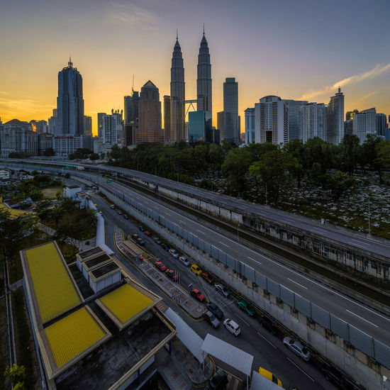 Petronas towers amidst buildings in city during sunset