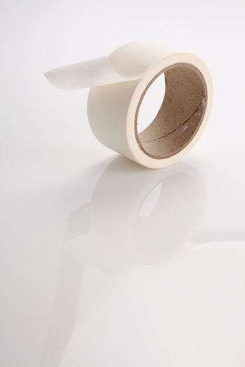 Roll of masking tape on white Beige Circle Fix  Isolated Rollercoaster Adhesive Adhesive Tape Concept Element Equipment Indoors  Label Masking Masking Tape No People Object Office Supply Packing Paper Reel Round Sticky Tape Tool White Background