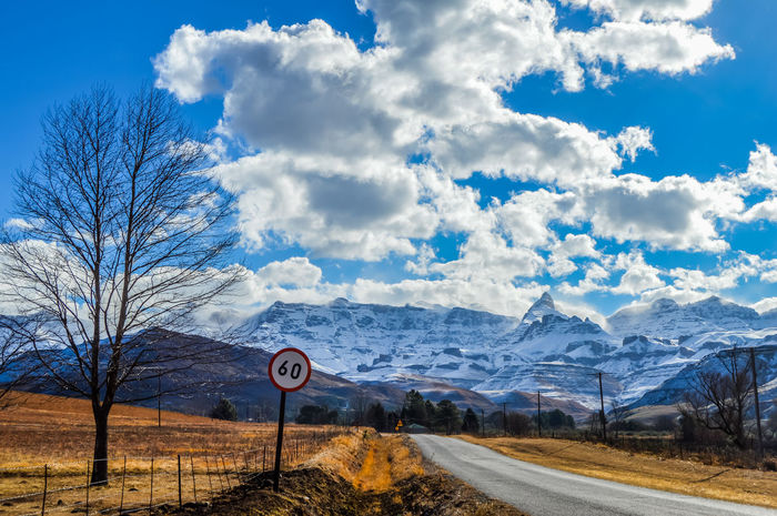Picturesque landscape with a bare tree on roadside with snow clad drakensberg mountains on the background Snow In South Africa South Africa Bare Tree Beauty In Nature Cloud - Sky Cold Temperature Direction Drakensberg Nature No People Outdoors Plant Road Road Sign Scenics - Nature Sign Sky Snow Snowcapped Mountain Speed Limit Sign The Way Forward Transportation Tree Underberg Winter EyeEmNewHere