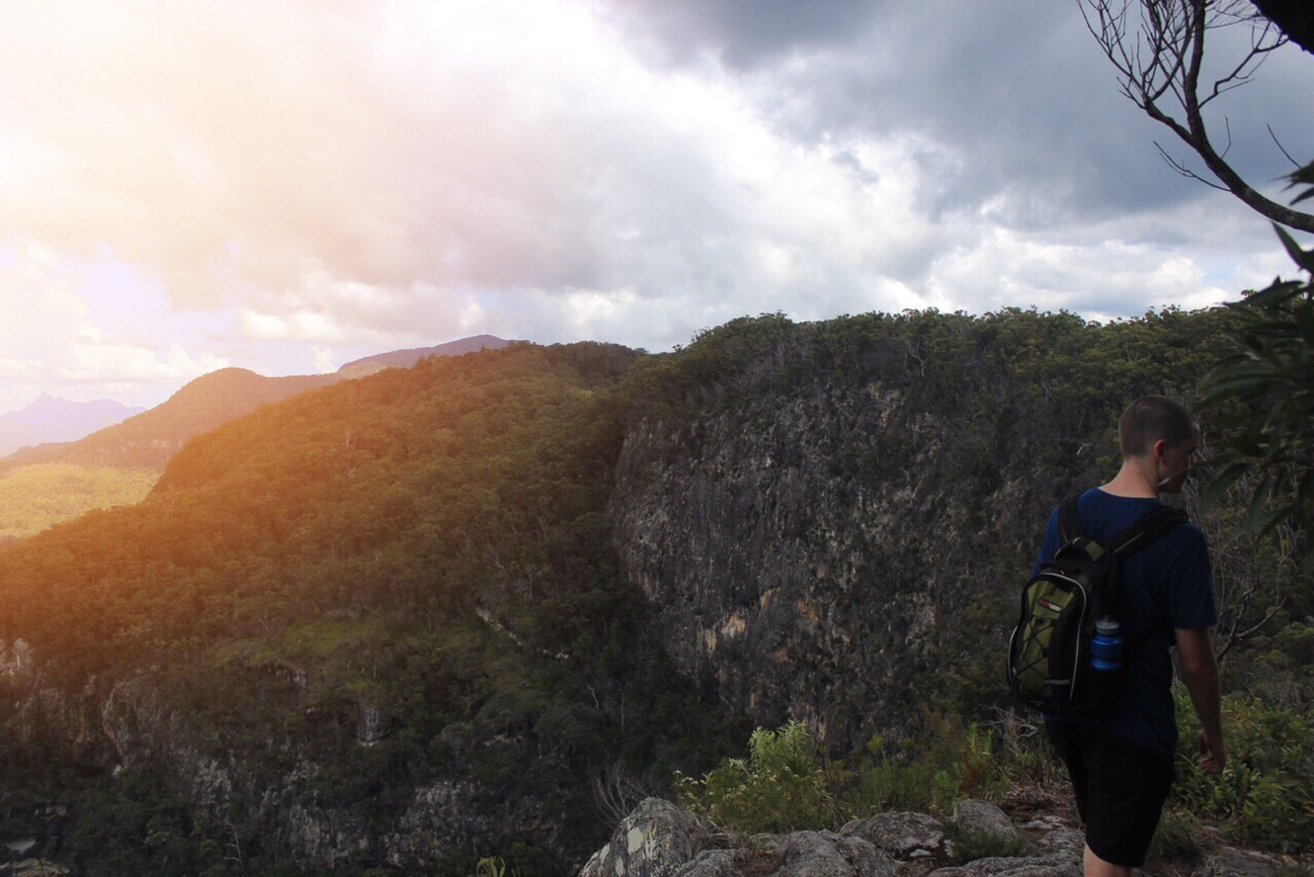 sky, lifestyles, mountain, leisure activity, cloud - sky, men, landscape, nature, tranquil scene, tranquility, rock - object, standing, hiking, scenics, rear view, casual clothing, full length, beauty in nature