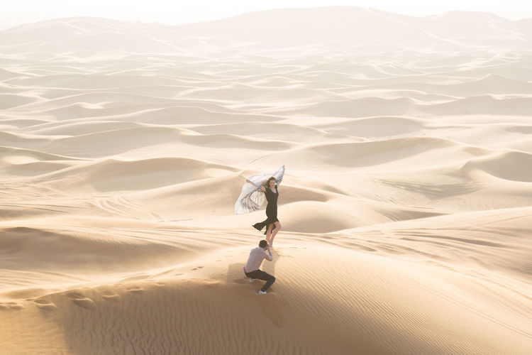 High angle view of man photographing woman at desert