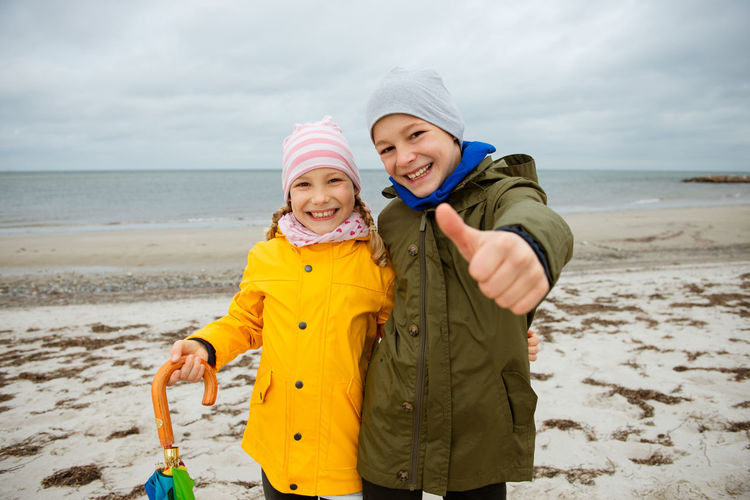 Portrait of smiling boy with sister showing thumbs up sign at beach