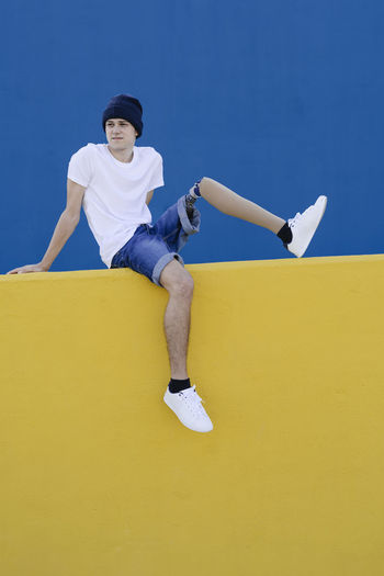 Full length of young man sitting against yellow wall