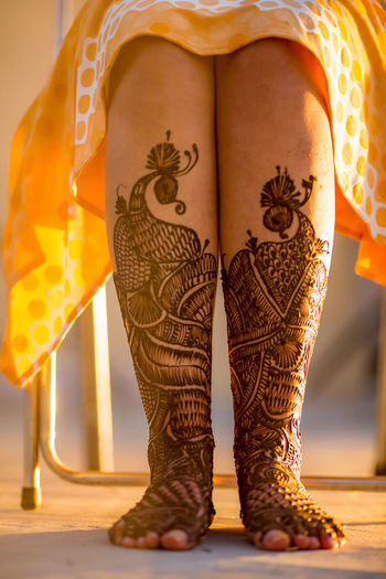 Low section of bride with henna tattoo on legs