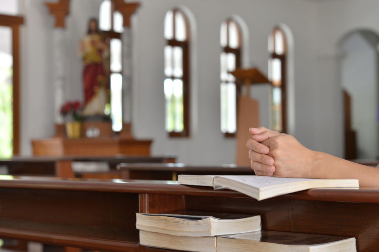 Cropped Hands Of Person Praying Over Bible At Church