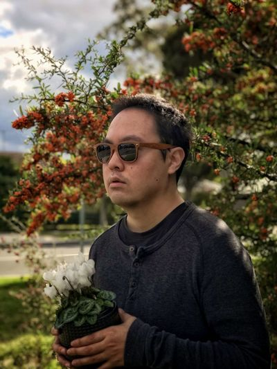 Portrait of young man holding potted white flowering cyclamen plant against yellow rowan berry tree.