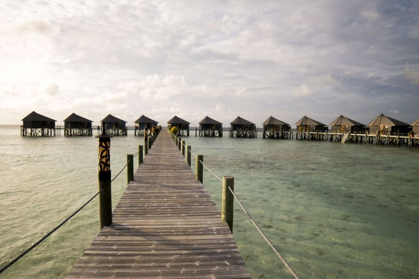 Water villas at Komandoo Resort in Maldives during sunrise Architecture Beauty In Nature Building Exterior Built Structure Day Jetty Komandoo Maldives Maldives Resorts Nature Outdoors Pier Real People Sea Sky Sunrise Tranquil Scene Tranquility Water Water Villa