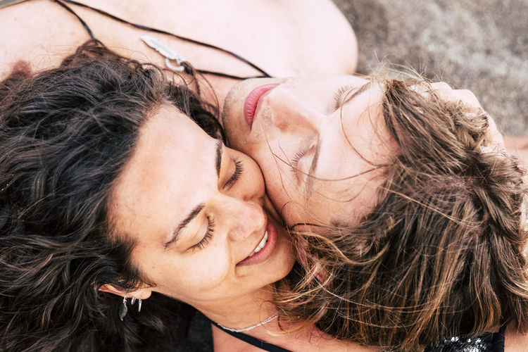 Close-up of smiling man and woman lying on sand at beach