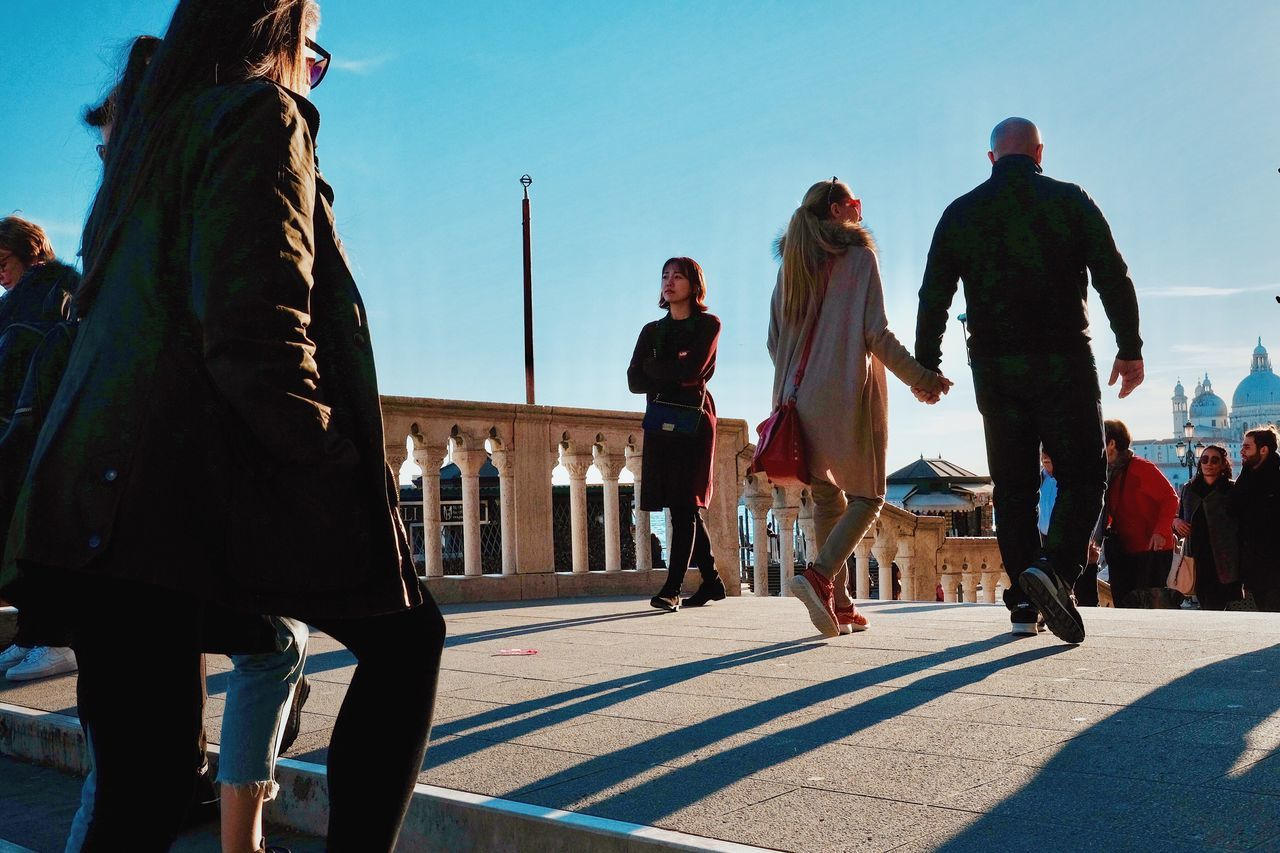 real people, sunlight, lifestyles, leisure activity, day, outdoors, casual clothing, full length, walking, men, togetherness, large group of people, sky, friendship, city, young adult, people, adult
