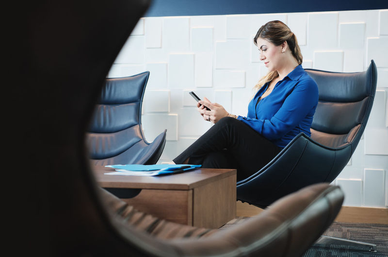 Woman using mobile phone while sitting on chair