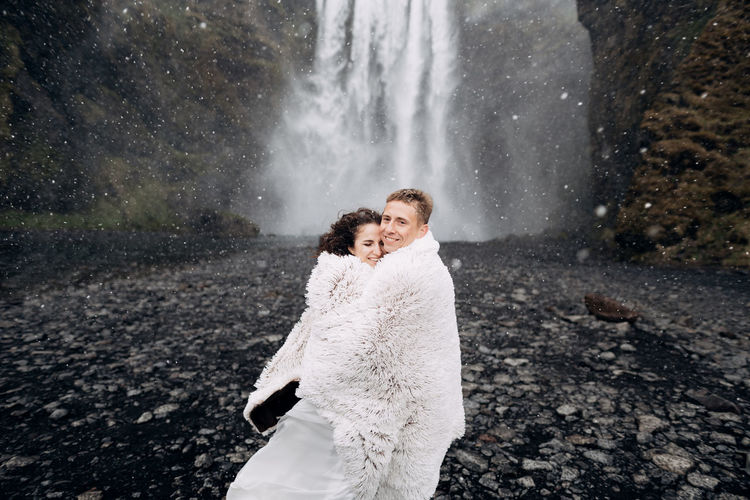 Rear view of couple standing against waterfall