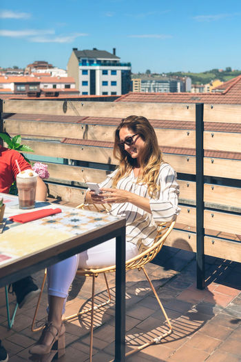Woman sitting on table at outdoor cafe