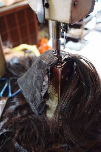 Wig making Sewing Machinery Close-up Sewing Machine Thread Focus On Foreground Textile Manufacturing Equipment Industry Hanging Day Indoors  Equipment Metal Textile Industry Art And Craft Machine Part
