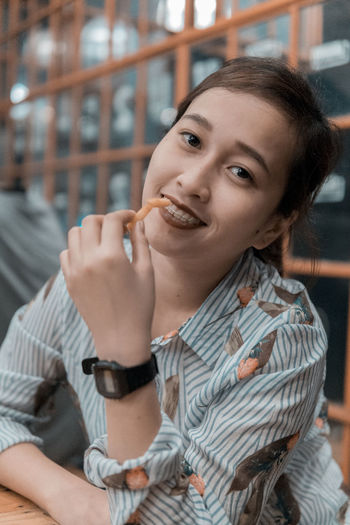 Portrait Of Smiling Young Woman Having French Fries