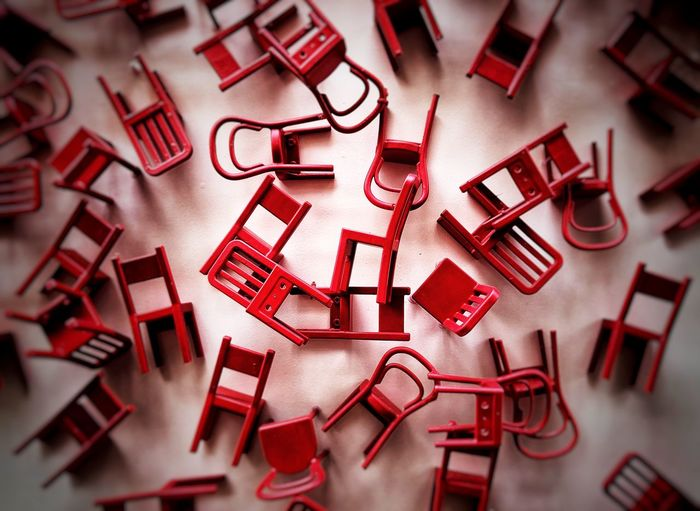 Directly above view of scattered red chairs on floor