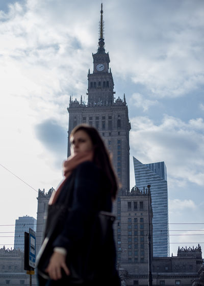 Low angle view of woman standing by buildings against sky