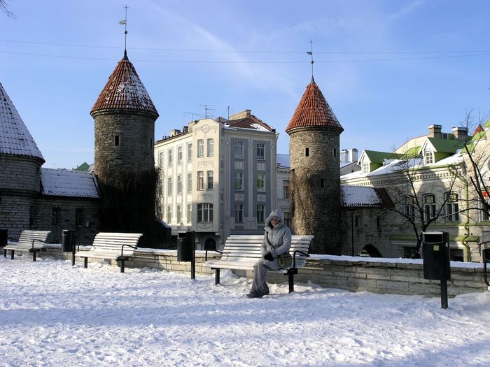 Man sitting on bench against building during winter