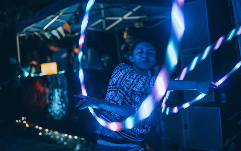 Woman performing with illuminated hoops at night at party