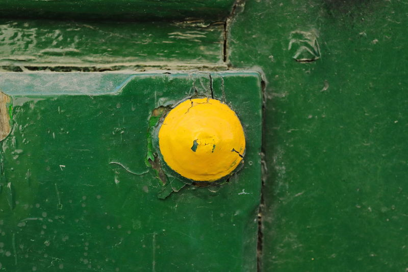 Close-up of yellow door on green wall