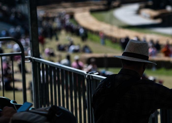 Rear view of man sitting on railing