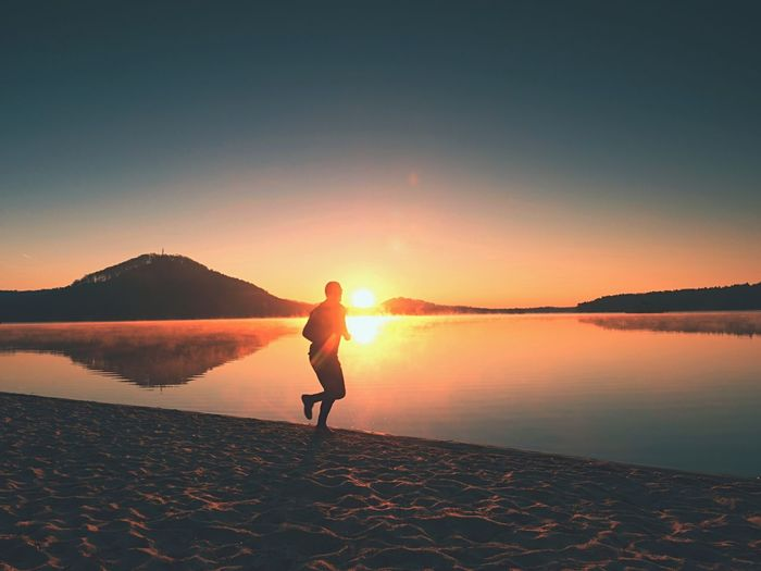 Man running onbeach against backdrop of beautiful sunset. sand of mountain lake with foot trails.
