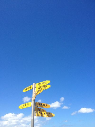 Low Angle View Of Arrow Sign Against Blue Sky