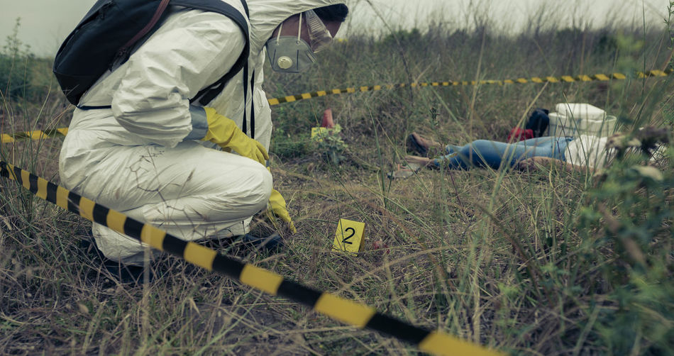 Detective wearing protective suit crouching on land at crime scene