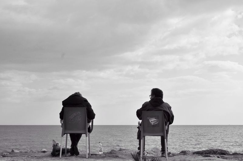 Rear view of man and woman sitting on chair at shore against cloudy sky