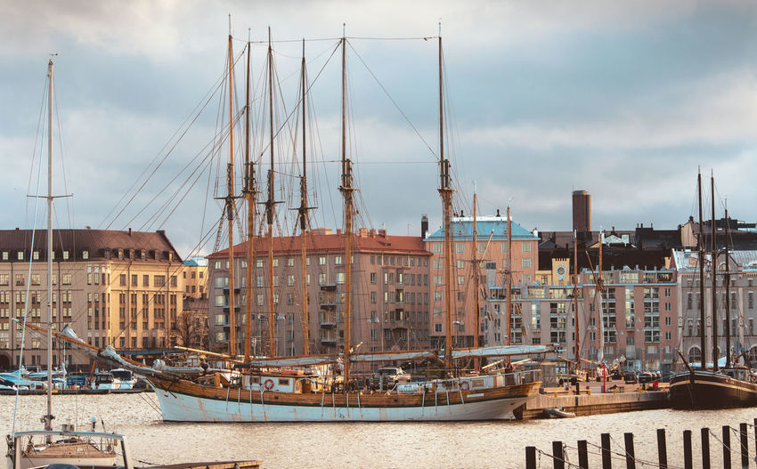 Tall ship moored at harbor in city